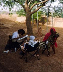 Louise Cutler drawing a women in the village of Golmi (Africa)